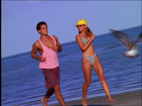 vídeos de stock, filmes e b-roll de couple in swimsuits jogging on beach - 1990