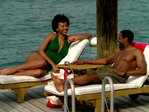 vídeos y material grabado en eventos de stock de ms,  couple in swimsuits talking,  sitting on lounge chairs on pier,  harbour island,  bahamas - traje de baño de una pieza