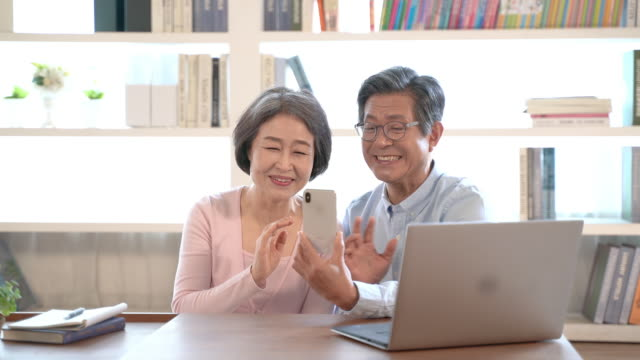 couple in their sixties doing a video call with smartphone and getting happy - south korea couple stock videos & royalty-free footage