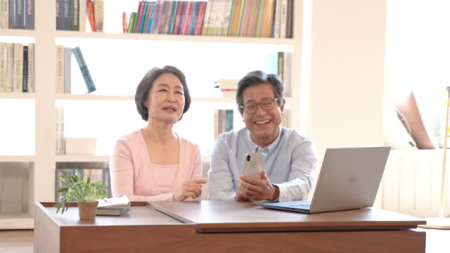 couple in their sixties using smartphone and getting happy - south korea couple stock videos & royalty-free footage