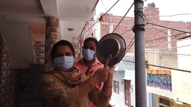 couple in their terrace balcony as they bang their utensils of steel in india to make sounds and noise to greet the medical workers and the frontline essential workforce to encourage them and uplift their spirits during the global crisis of covid19 - cooking pan stock videos & royalty-free footage