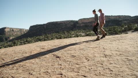 vídeos y material grabado en eventos de stock de pareja en sus años 20 caminatas en el desierto - tartán
