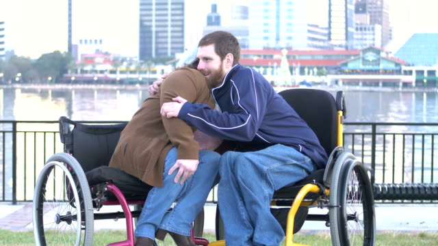couple in wheelchairs on city waterfront hugging - hugging self stock videos & royalty-free footage