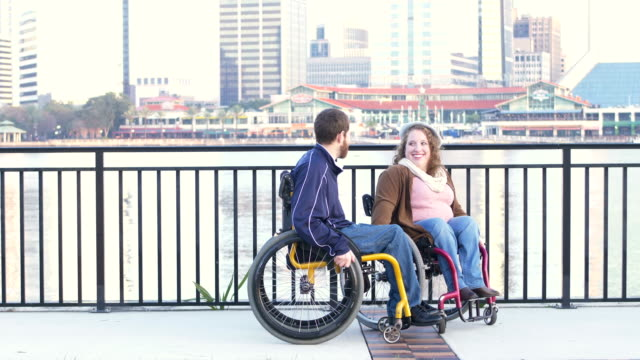 couple in wheelchairs on city waterfront - rolling stock videos & royalty-free footage