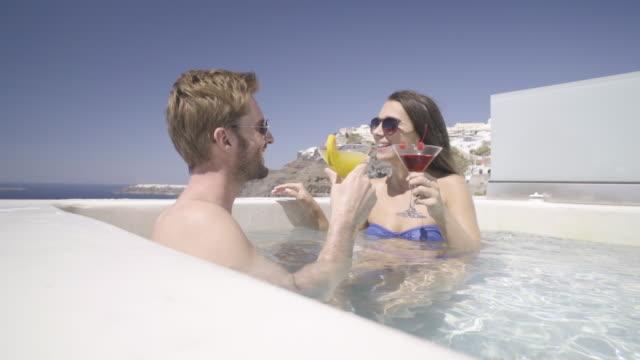 vídeos y material grabado en eventos de stock de couple in whirlpool on sunny day cheering with cocktails slow motion - cóctel tropical