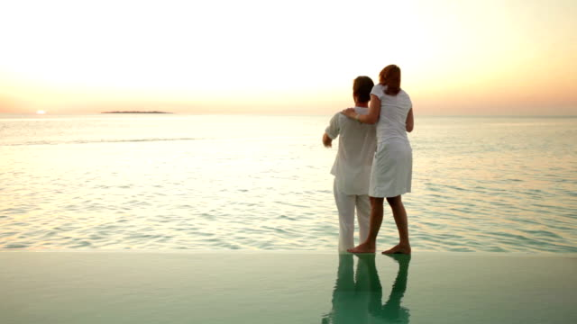 couple in white at private pool - infinity pool stock videos & royalty-free footage