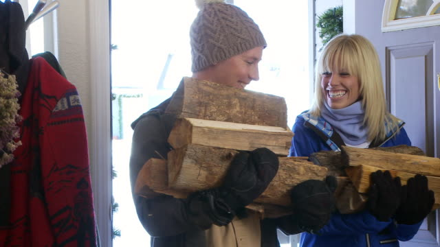 Couple in winter clothes bringing fire wood in through the front door / Bellevue, Idaho, United States
