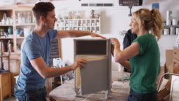 Couple in workshop upcycling and restoring cabinet together - shot in slow motion