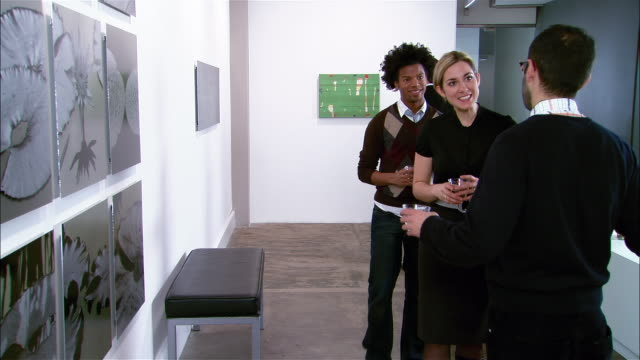 couple introducing themselves to man at gallery opening - boyfriend stock videos & royalty-free footage