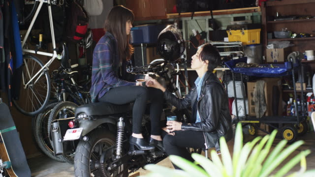 lgbt couple is in the garage fixing a motorcycle and drinking tea together - スポーツヘルメット点の映像素材/bロール