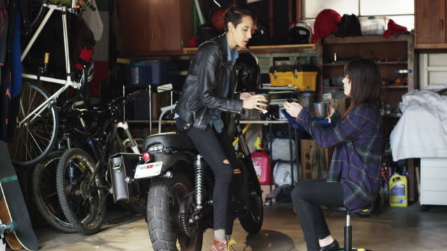 lgbt couple is in the garage fixing a motorcycle and drinking tea together - helmet motorcycle stock videos and b-roll footage
