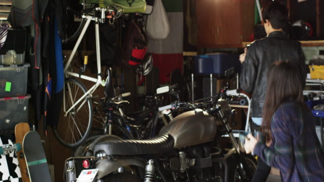 lgbt couple is in the garage fixing a motorcycle and drinking tea together - crash helmet stock videos and b-roll footage