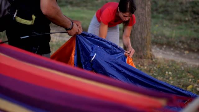 カップルは、自然の屋外のキャンプ テントを準備しています - 寝袋点の映像素材/bロール