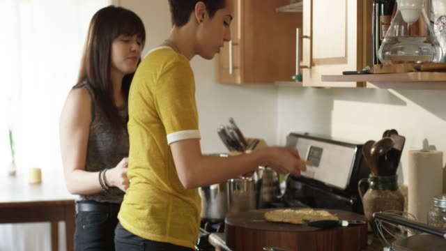 vídeos y material grabado en eventos de stock de a lgbt couple is preparing dough, cooking and eating pizza in their kitchen - sin mangas