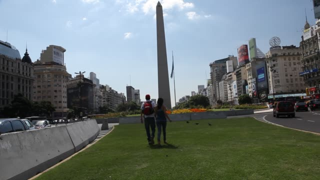 vídeos y material grabado en eventos de stock de a couple is walking to the obelisk the obelisco de buenos aires is a national historic monument and icon of buenos aires located in the plaza de la... - obelisco de buenos aires