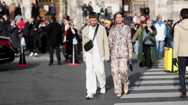 stockvideo's en b-roll-footage met couple jeansebastien rocques wearing beige jacket fanny and alice barbier wearing suit with graphic print seen outside berluti during paris fashion... - herfst winter collectie