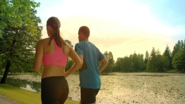 stockvideo's en b-roll-footage met slo mo ts paar joggen langs het meer in de zon - sunshine lake