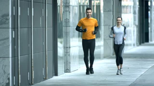 vídeos de stock, filmes e b-roll de hd câmera lenta: casal jogging ao longo da calçada - inverno