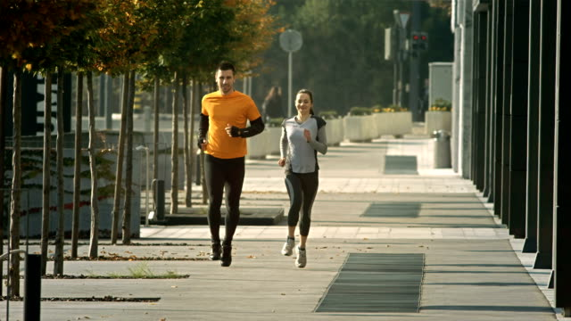 HD SLOW MOTION: Couple Jogging Along Treelined Walkway