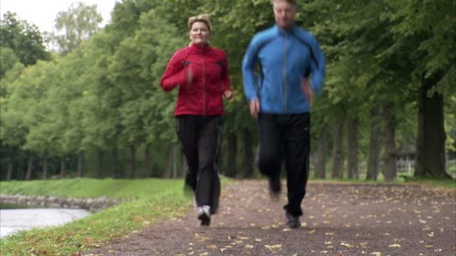 couple jogging alongside a canal, sweden. - 異性情侶 個影片檔及 b 捲影像