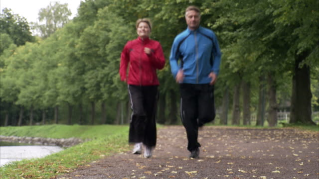 couple jogging alongside a canal, sweden. - cinquantenne video stock e b–roll
