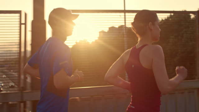 slo mo ts couple jogging in the city at sunset - jogging stock videos & royalty-free footage