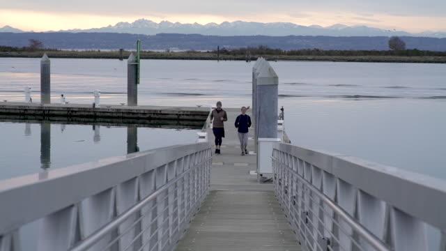 Couple jogging on pier to bridge.