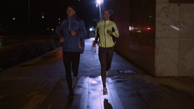 SLO MO TS Couple jogging on rainy street at night