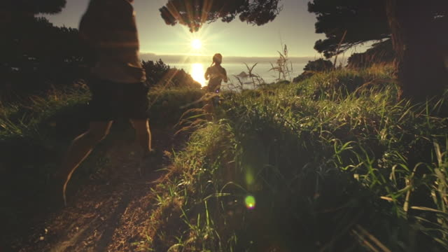 MS SLO MO POV Couple jogging on trail on Pacific Coast / Port Orford, Oregon, United States