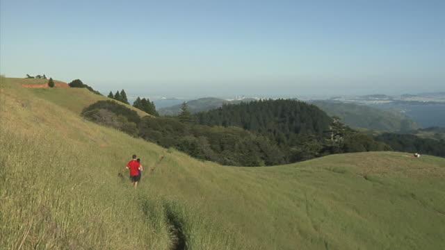 WS PAN HA Couple jogging through rolling hills, person flying kite nearby, Mount Tamalpais, California, USA