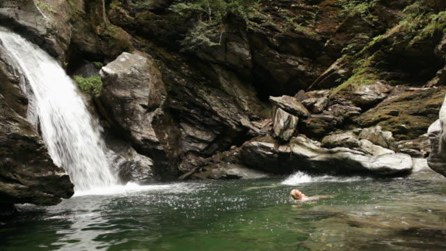 ms couple jumping in and swimming in the river by the waterfall / stowe, vermont, united states - stowe vermont stock videos & royalty-free footage