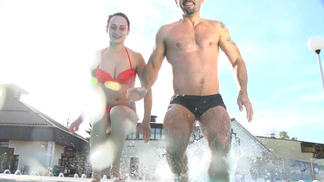 - super zeitlupe, hd: paar-springen in den pool - freibad stock-videos und b-roll-filmmaterial