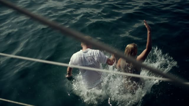 couple jumping into sea from a boat deck - balearic islands stock videos and b-roll footage