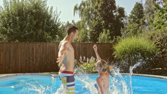 vidéos et rushes de au ralenti couple de cs en train de sauter dans la piscine ensemble - clôture jardin