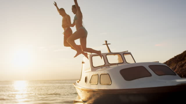 vídeos de stock e filmes b-roll de slo mo couple jumping off a boat in sunset - par