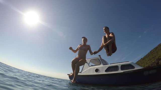 vídeos de stock e filmes b-roll de pov couple jumping off a boat into the sea - flutuar no ar