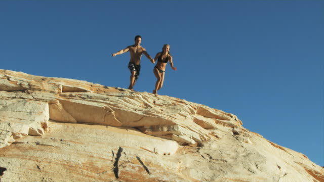 couple jumping off a cliff into the water - diving into water stock videos & royalty-free footage