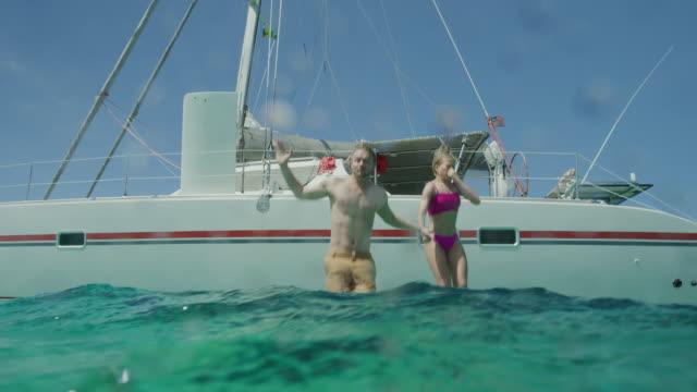 couple jumping off boat and swimming underwater in ocean / tobago cays, saint vincent and the grenadines - badbyxor bildbanksvideor och videomaterial från bakom kulisserna