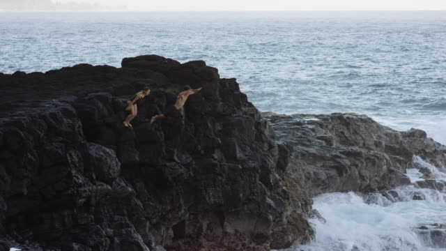 SLO MO paar springen van rots in de Oceaan
