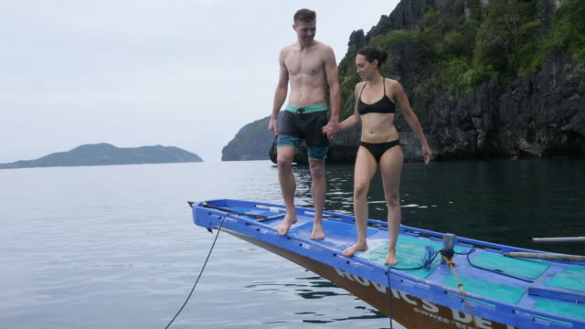 couple jumping off front of boat - undersea stock videos & royalty-free footage
