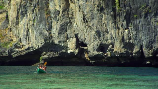 vídeos de stock e filmes b-roll de ws couple kayaking in sea, cliff in background / krabi, thailand - província de krabi