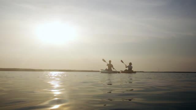 vidéos et rushes de couple kayaking in water at sunset - kayak sport