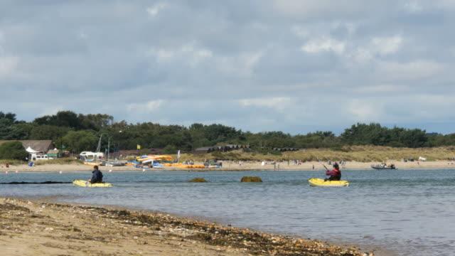 vídeos y material grabado en eventos de stock de couple kayaking near the shore, beach watersports in background - studland heath