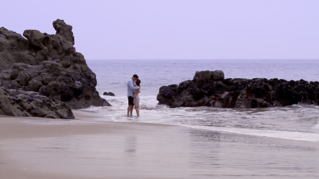 vidéos et rushes de couple kiss and playfully run down beach - affectueux