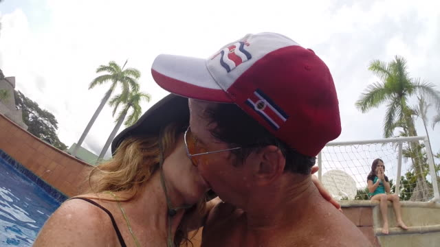 stockvideo's en b-roll-footage met couple kiss at resort with little girl in background - kelly mason videos