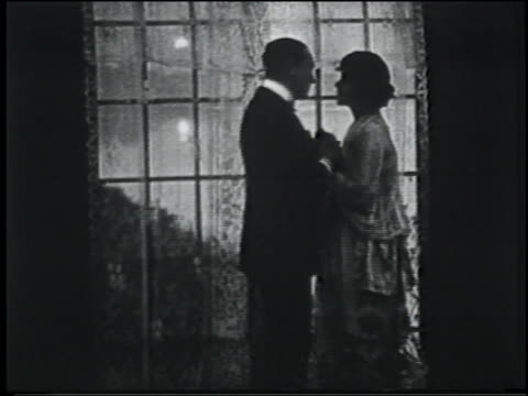 B/W 1920 couple kiss + hug in front of window / they turn to window