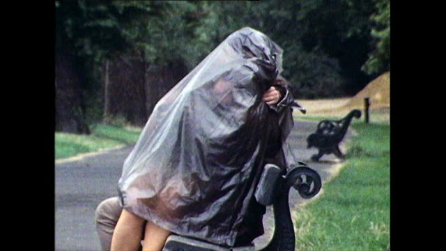 couple kiss on park bench hiding under plastic sheet ; 1971 - couple relationship stock videos & royalty-free footage