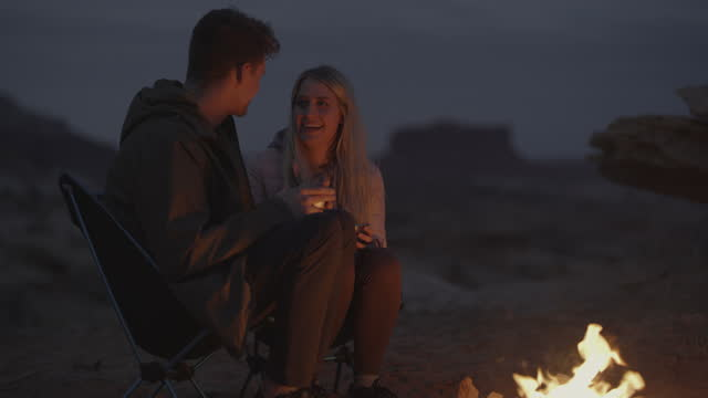 couple kissing and drinking near campfire at dusk / moab, utah, united states - outdoor chair stock videos & royalty-free footage