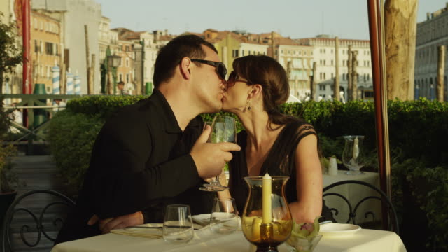 MS Couple kissing and having glass of wine in outdoor cafe / Venice,Veneto
