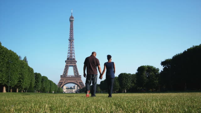 couple kissing and holding hands in front of the Eiffel tower